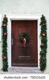 Christmas decoration of the door with a beautiful traditional wreath. Celebrating Christmas, decorating the house.