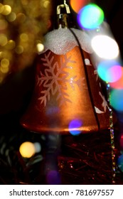 Christmas Decoration- Elegant orange Christmas bell ornament decorated by white snowflake and colorful bokeh in the background