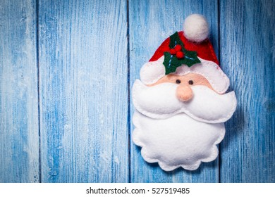 Christmas decoration, felt Santa Claus, over old wood background