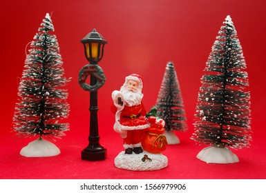 Christmas decoration with figures and snowy trees on red background Spain November 09 2019