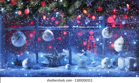 Christmas Decoration With Fir Branches And Balls At The Snow-Covered Window