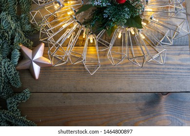 Christmas decoration with fir tree and garland lights on old wooden background.