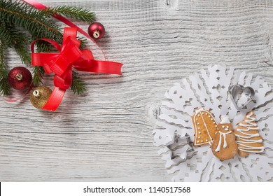Christmas decoration. fir tree twig, balls, red ribbon and gingerbread cookies on a white wooden table. Empty space for text.