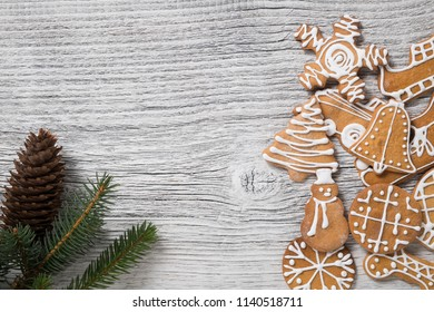 Christmas decoration. fir tree twig and gingerbread cookies on a white wooden table. Empty space for text.