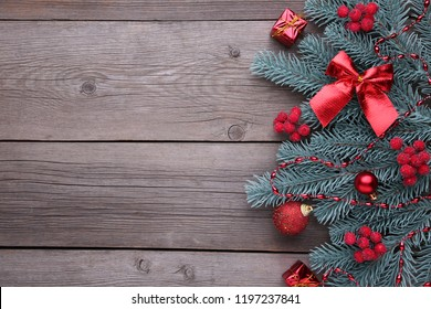 Christmas decoration. Fir-tree branch with balls, bumps, berries of viburnum and gifts on a grey wooden background
