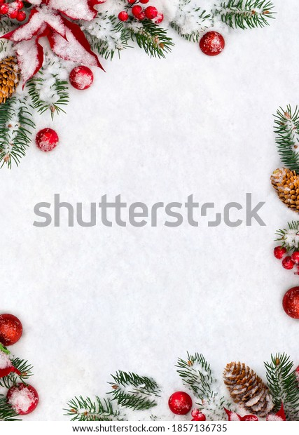 Christmas decoration. Frame of branches christmas tree, flower of red poinsettia, brown natural spruce cones, red ball, red berries on snow with space for text. Top view, flat lay