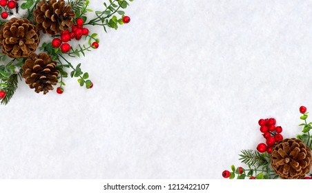 Christmas decoration. Frame of twigs christmas tree, brown natural pine cones and red berries on snow with space for text. Top view, flat lay