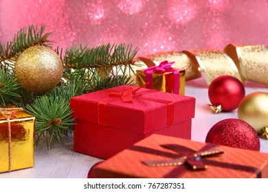 Christmas decoration with gift boxes, colorful christmas balls and christmas tree on a blurry, sparkling and fabulous background..