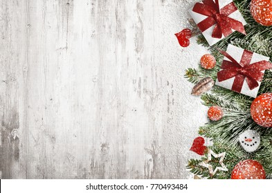 Christmas decoration and gift boxes covered by snowflakes over the white wooden background, with free space for text input, logo, etc.