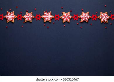 christmas decoration and gingerbread cookies on dark blue background with empty copy space for your text. holiday, celebration and cooking concept. new year and christmas postcard