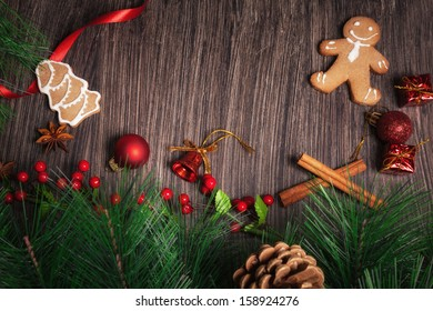 Christmas decoration with Gingerbread cookies and Christmas ornaments on rustic wood.