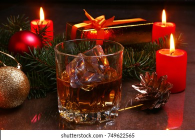 christmas decoration with glass of cognac or whiskey, red candles, gift box and christmas tree. Selective focus.
