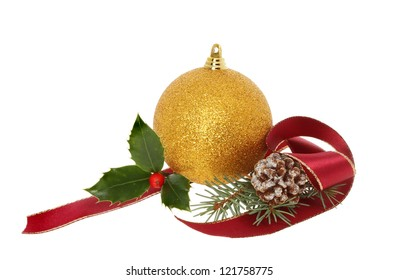 Christmas decoration of gold bauble with holly, ribbon pine cone and leaves