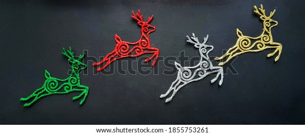 Christmas decoration, gold, silver, red, green deer in sparkles on a black background. in the tones of a fabulous New Year's mood. Merry Christmas