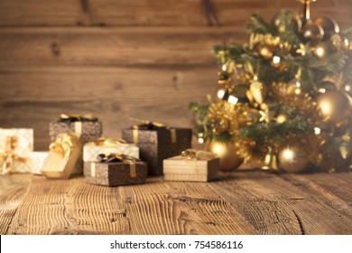 Christmas decoration in golden and brownish aesthetics with presents in boxes, golden baubles, all on rustic wooden background.
