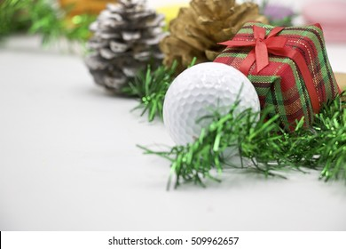 Christmas decoration for golfer. There are golf ball, Christmas ornament and pine cone on white background.