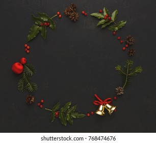 Christmas decoration handmade frame background, top view with copy space on black table. Creative diy craft hobby, xmas wreath with pine fir and holly leaves