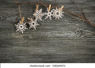 Christmas decoration hanging on branch against wooden background