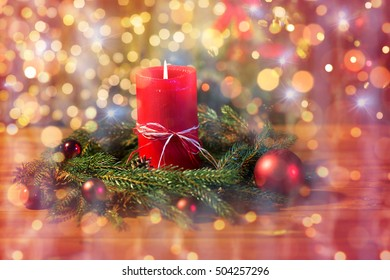 christmas, decoration, holidays and advertisement concept - close up of natural green fir wreath with red burning candle over lights