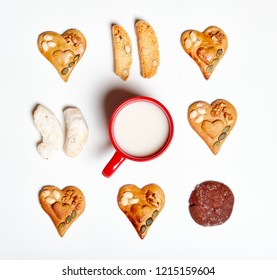 Christmas decoration isolated on white background. Homemade gingerbread cookies and a cup of milk on white background, lots of heart shapes.
