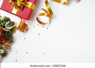 Christmas decoration isolated white on the left. Red and gift box and golden ribbon with floral ornament. Top view. Horizontal and diagonal composition.