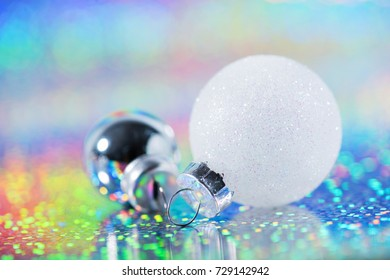 Christmas decoration laying on the rainbow glittering background. New year ball.