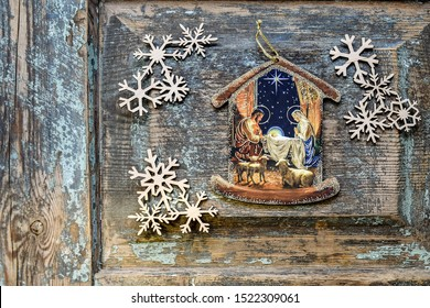 Christmas decoration: Nativity scene image and Wooden snowflakes laid on an old wooden surface. Top view. Selective focus. Copy space.