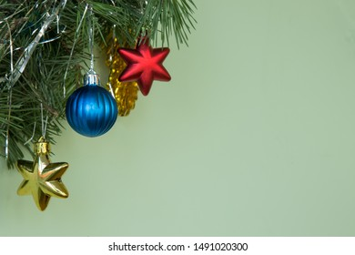 Christmas decoration. Natural pine branches on a green background ith blue ball and yellow Xmas red stars and New Year's toys. Copy space.