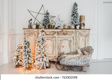 Christmas decoration on ancient vintage old commode chest of drawers. Hand made craft gifts, candels and a tree at background.