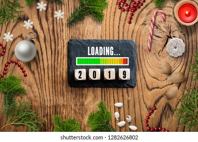 Christmas decoration on rustic wooden background and a loding bar for 2019 on a slate plate