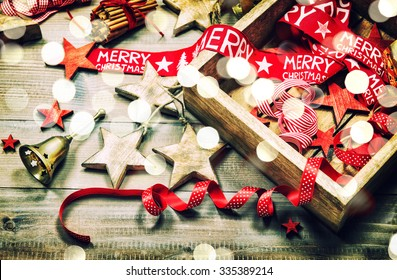 Christmas decoration and ornaments on rustic wooden background. Retro style dark colored picture with light effects