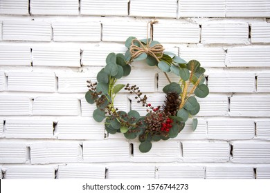 Christmas Decoration ornaments with wreath evergreen isolated on white brick wall background. Handmade noel festive hanging
