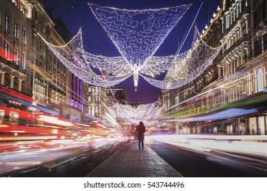 Christmas decoration over a lonely woman surrounded by traffic at Regent street, London, UK.