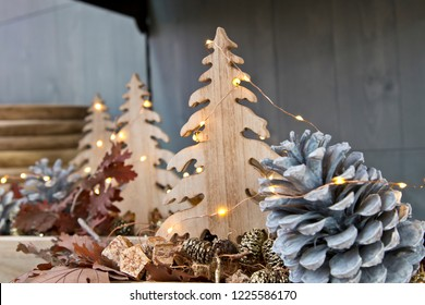 Christmas decoration with pine cones and wooden christmas trees