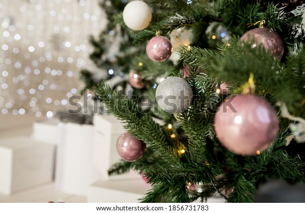 Christmas Decoration. Pink, silver and white Balls on Christmas tree branch. Holiday Card.Christmas toy ball hanging on branch of spruce. New year tree decorated with a garland.Stylish Christmas tree