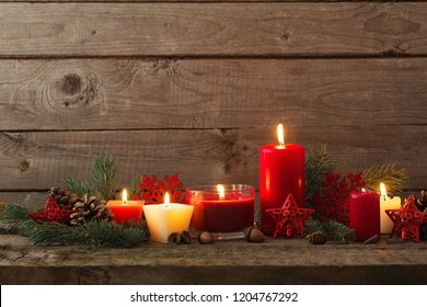 Christmas decoration with red candles on wooden background