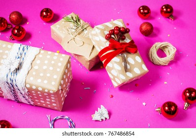 christmas decoration: red glass christmas balls and gifts on pink background