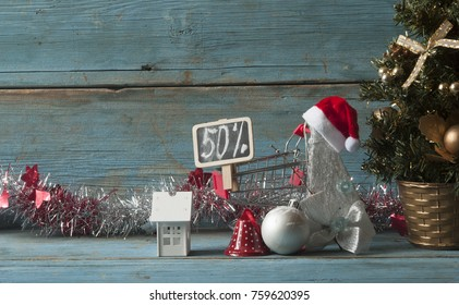 Christmas decoration with Santa hat and chalkboard with discounts on wooden background