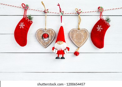 Christmas decoration with Santa on white wooden background. Red Christmas socks, Santa Claus and Christmas hearts. Copy space