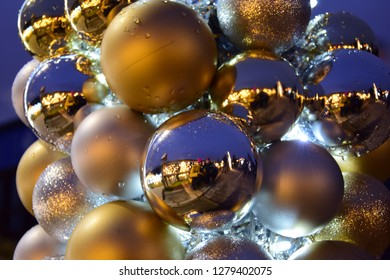 Christmas decoration with shiny reflections and showing copule of people like in crazy mirror. Baubles in silver and gold colors on the holidays mood, snow and winter time. Abstract concept.