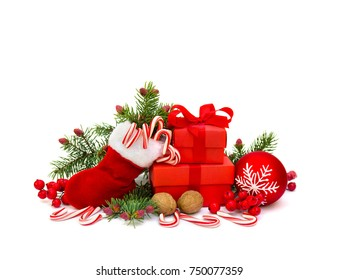 Christmas decoration with christmas stocking, branch of spruce, candies, walnut, berry, gift boxes and Christmas ball with snowflake on white background with space for text.