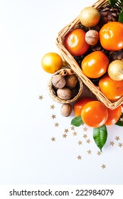 Christmas decoration with tangerines, cones, walnut, golden baubles and stars over white background. Holiday greeting card. Space for your text.