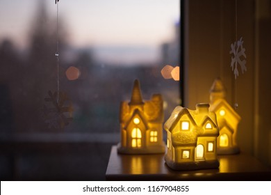 Christmas decoration of three ceramic lamp houses glowing with warm light  stand against the window with twilight cityscape. concept of a cozy home, buying real estate
