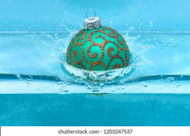 Christmas decoration or toy for Christmas tree swim in pool. Festive decoration for Christmas tree, green ball dropped into water with splashes, blue background. Holidays and vacation concept.
