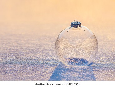 Christmas decoration transparent glass ball with snowflakes shiny in sunset sunlight on snow surface . Happy New year greeting cards concept