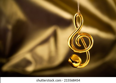 Christmas decoration, treble clef jingle bell on silky gold/green background.
