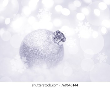 Christmas Decoration with White Ball in the Snow on the Blurred Background with Lights. Greeting Card with Space for Your Text