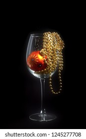 A Christmas decoration wine glass on black background with glass ball and golden perls