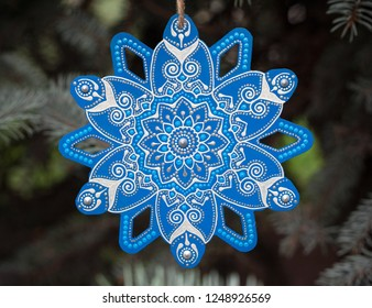 Christmas decoration, woden snowflake star painted with blue color and indian mandala flower made by dots on background of blurred pine tree brunches.