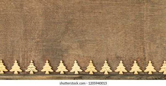 Christmas decoration wooden background with row of small wooden fir trees